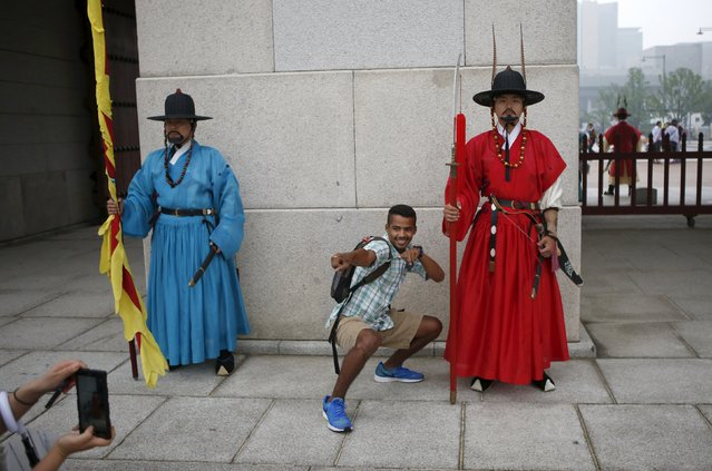 A tourist poses for photographs next to workers wearing traditional dress while attending the daily re-enactment of the changing of the Royal Guards at Gyeongbok Palace in central Seoul, South Korea, July 13, 2015. (Photo by Kim Hong-Ji/Reuters)