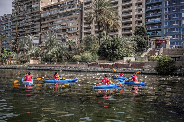 Volunteers riding in kayaks take part in a water-waste removal and cleanup campaign in the Nile river off the island of Manial in Egypt's capital Cairo on March 7, 2020. Early one morning in Cairo, a flotilla of some 300 environmental determined activists paddle their kayaks across the Nile, fishing out garbage from the mighty waterway that gave birth to Egyptian civilisation but now faces multiple threats. In the past three years they say they have picked some 37 tonnes of cans, plastic bottles, disposable bags and other trash from the waters and shores along the Nile in Egypt. (Photo  by Khaled Desouki/AFP Photo)