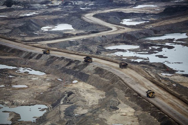 Giant dump trucks haul raw tar sands at the Suncor tar sands mining operations near Fort McMurray, Alberta, September 17, 2014. In 1967 Suncor helped pioneer the commercial development of Canada's oil sands, one of the largest petroleum resource basins in the world. (Photo by Todd Korol/Reuters)
