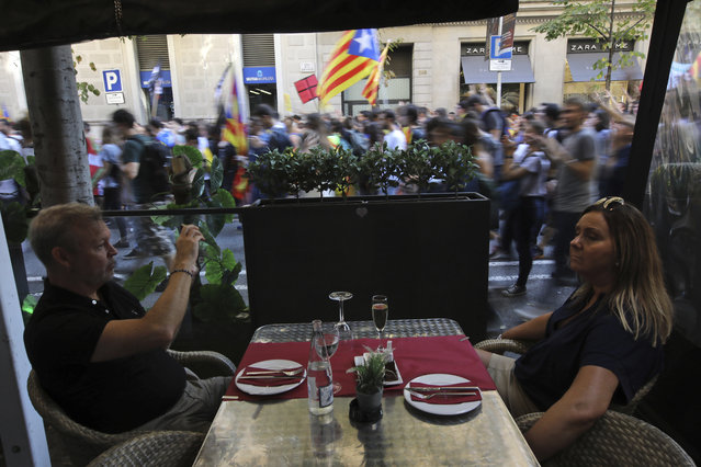 People watch from a restaurant as students march past during a protest against the Spanish government announcement of implementing the article 155 in the Catalonia region, in Barcelona, Spain, Thursday October 26, 2017. The Catalan parliament is due to meet to discuss Spanish government's plans to remove the leaders of the regional government. (Photo by Emilio Morenatti/AP Photo)