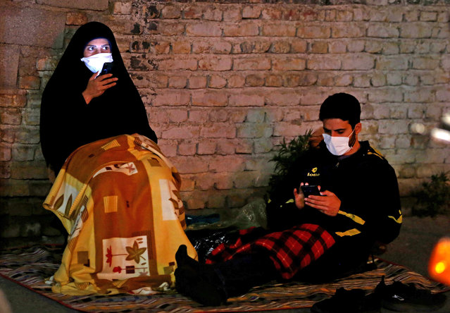 Iranians wearing face masks against the Covid-19 coronavirus attends Laylat al-Qadr prayers, one of the holiest nights during the Muslim fasting month of Ramadan, outside a mosque in the Tehran, on May 13, 2020. (Photo by Atta Kenare/AFP Photo)