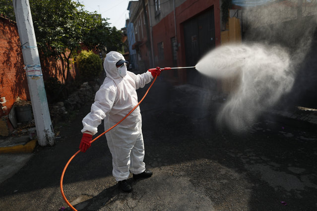A public safety worker sprays a disinfectant solution in the streets of the El Rosario neighborhood, which had seen a recent cluster of COVID-19 cases, in Xochimilco, Mexico City, Mexico, Friday, May 29, 2020. (Photo by Rebecca Blackwell/AP Photo)