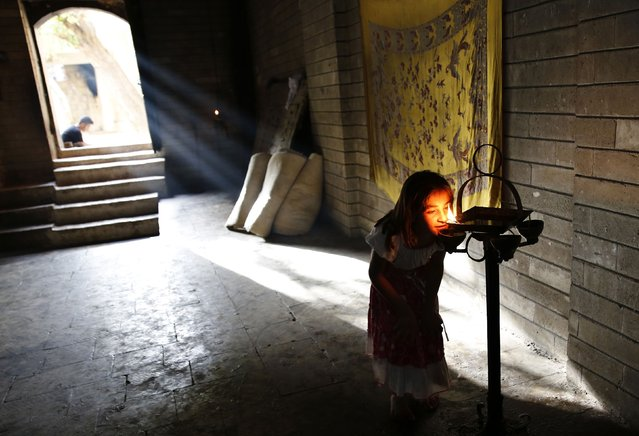 A displaced girl from the  minority Yazidi sect, who fled violence in the Iraqi town of Sinjar, worships at their main holy temple Lalish in Shikhan September 20, 2014. Followers of an ancient religion derived from Zoroastrianism, the Yazidi fled their homeland in the Sinjar mountains as Islamic State militants, who see them as devil worshippers, seized towns and carried out mass killings in August. (Photo by Ahmed Jadallah/Reuters)