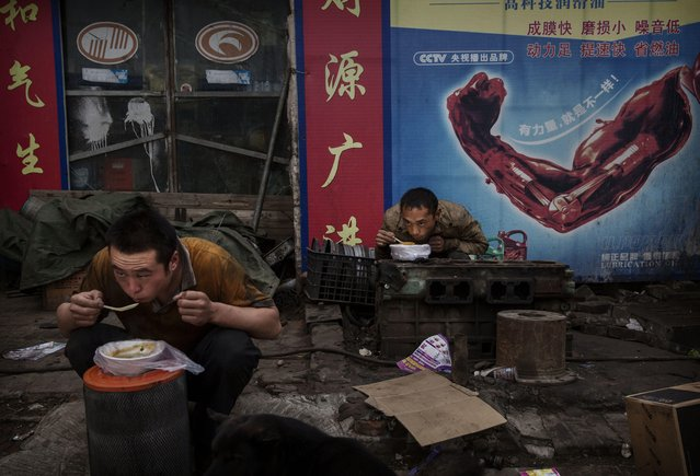 Chinese laborers eat breakfast at a local market on September 26, 2014 in Beijing, China. (Photo by Kevin Frayer/Getty Images)