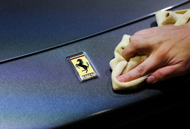 An employee polishes the front of a Ferrari car during the media day at the Frankfurt Motor Show (IAA) in Frankfurt, Germany, September 14, 2015. (Photo by Kai Pfaffenbach/Reuters)