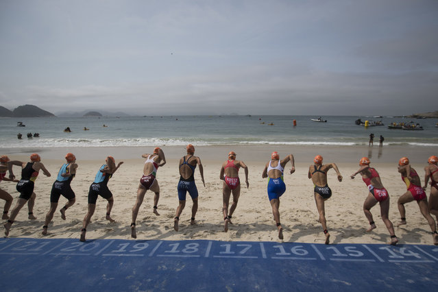 Competitors run to the water for the start of the women's triathlon event at the 2016 Summer Olympics in Rio de Janeiro, Brazil, Saturday, August 20, 2016. (Photo by Felipe Dana/AP Photo)