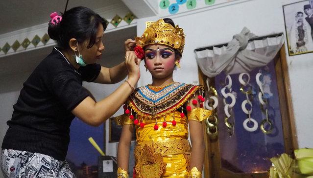 11-year-old Balinese dancer girl Intan puts on makeup before she performs Mergapati Dance at a village event in Banjar Wangaye Kelod, Denpasar, Bali, Indonesia on November 19, 2017. (Photo by Mahendra Moonstar/Anadolu Agency/Getty Images)