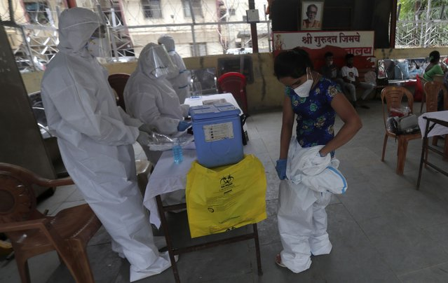 A health worker removes her personal protective equipment after completing screening of residents for COVID-19 symptoms in Dharavi, one of Asia's biggest slums, in Mumbai, India, Friday, June 26, 2020. India is the fourth hardest-hit country by the pandemic in the world after the U.S., Russia and Brazil. (Photo by Rafiq Maqbool/AP Photo)