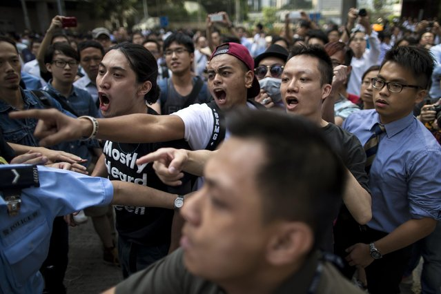 Pro-democracy protesters shout at anti-Occupy Central protesters as they clash in the Central financial district in Hong Kong October 13, 2014. (Photo by Tyrone Siu/Reuters)
