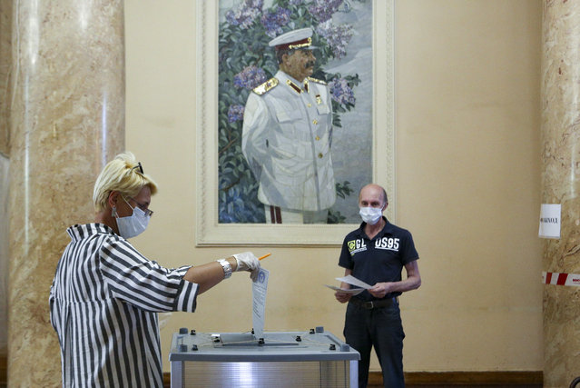 A woman, wearing a face mask and gloves to protect against coronavirus and observing social distancing guidelines, casts her ballot at a polling station with a portrait of former Soviet leader Josef Stalin on the wall in Volgograd, former Stalingrad, Russia, Wednesday, July 1, 2020. The vote on the constitutional amendments that would reset the clock on Russian President Vladimir Putin's tenure and enable him to serve two more six-year terms is set to wrap up Wednesday. (Photo by Dmitry Rogulin/AP Photo)