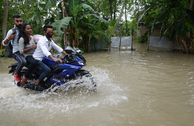 Youngsters ride a motorcycle through the flood water on a state highway in the flood affected Kamrup district of Assam, India, 13 July 2020. According to news reports, heavy rainfall during the past days has caused floods in the Assam state, leaving over one million people affected by it and over forty dead. (Photo by EPA/EFE/Stringer)