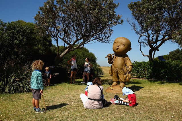 "People look at ""The Ascetic"" by Naidee Changmoh during the 2014 Sculptures by the Sea exhibition at Marks Park on October 23, 2014 in Sydney, Australia. (Photo by Cameron Spencer/Getty Images)"
