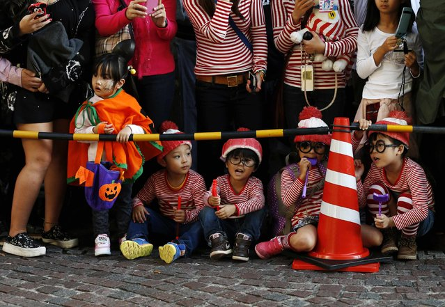 Spectators, dressed in costumes, wait for a Halloween parade in Kawasaki, south of Tokyo, October 26, 2014. (Photo by Yuya Shino/Reuters)