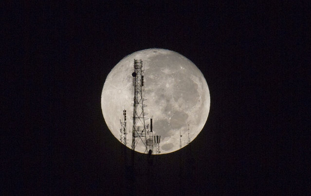 "A full moon silhouettes television and radio antennas on Boutilier Mountain, in Port-au-Prince, Haiti, early Sunday September 27, 2015. The full moon was seen prior to a phenomenon called a ""Super Moon"" eclipse that will occur Sunday night. (Photo by Dieu Nalio Chery/AP Photo)"