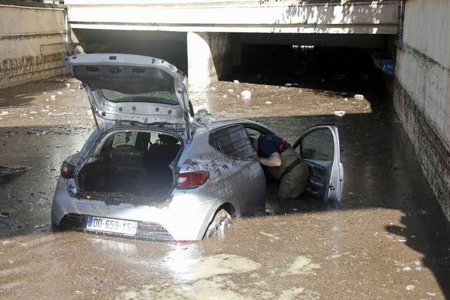 A French fireman inspects an abandoned car in muddy waters near an underpass after flooding caused by torrential rain in Cannes, France, October 4, 2015. (Photo by Eric Gaillard/Reuters)