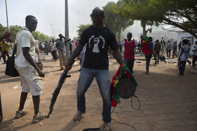 An anti-government protester carries a gun taken from the parliament building in Ouagadougou, capital of Burkina Faso, October 30, 2014. (Photo by Joe Penney/Reuters)