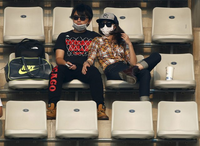 Spectators wearing masks watch men's singles match between David Goffin of Belgium and Andreas Seppi of Italy, on a polluted day at the China Open tennis tournament in Beijing, China, October 5, 2015. (Photo by Kim Kyung-Hoon/Reuters)