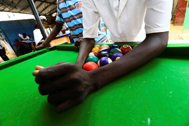 A boy places billiard balls on a table to form a triangle in Abu Shock IDPs camp in Al Fashir, capital of North Darfur, Sudan, September 6, 2016. (Photo by Mohamed Nureldin Abdallah/Reuters)