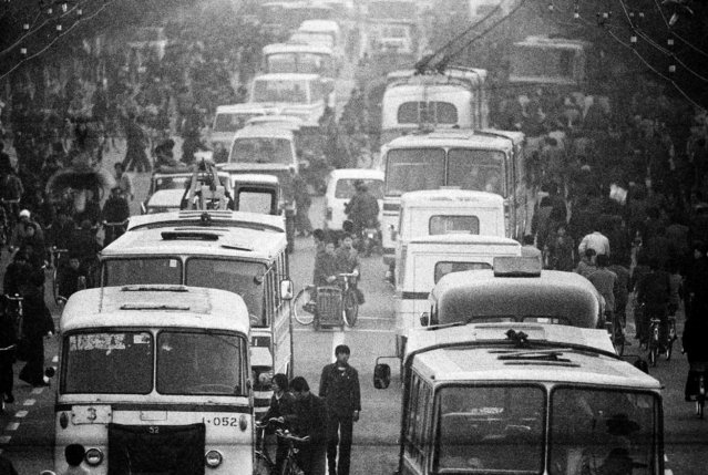 Buses and electrical trolley buses mingle with bicycles and pedestrians at a crossroad near Chongwenmen in Beijing in 1984. (Photo by Reuters/China Daily)