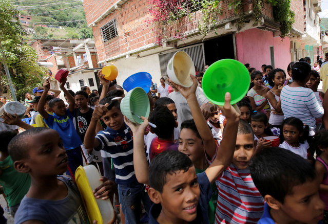 Children queue to wait to receive free food which was prepared by residents and volunteers on a street in the low-income neighborhood of Caucaguita in Caracas, Venezuela September 17, 2016. (Photo by Henry Romero/Reuters)