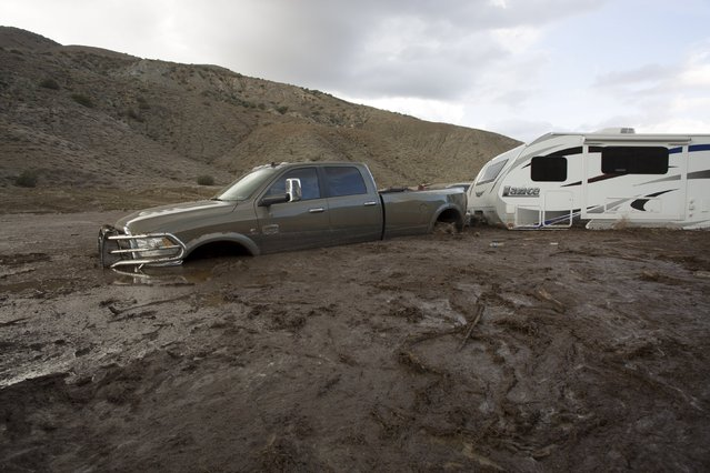 A truck and trailer remain mired in mud and debris on State Route 58 near Tehachapi, California, about 60 miles (97km) outside of Los Angeles October 17, 2015. (Photo by David McNew/Reuters)