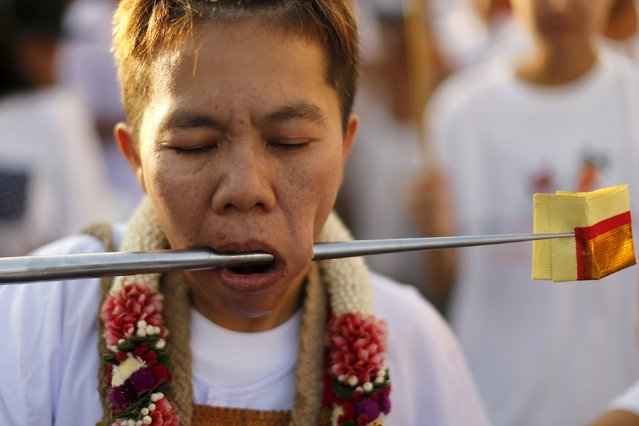 A devotee of the Chinese Jui Tui shrine walks with a spike pierced through her cheeks during a procession celebrating the annual vegetarian festival in Phuket, Thailand October 19, 2015. (Photo by Jorge Silva/Reuters)