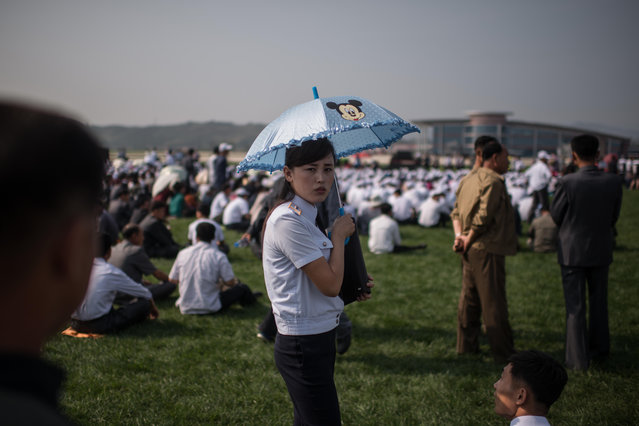 A woman holding an umbrella waits for the start of the first Wonsan Friendship Air Festival in Wonsan on September 24, 2016. (Photo by Ed Jones/AFP Photo)
