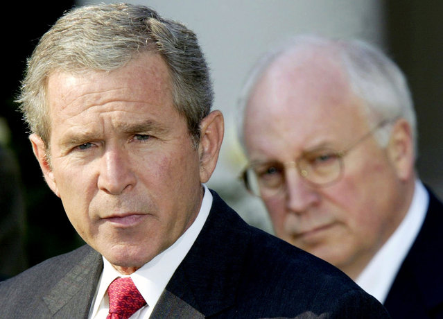U.S. President George W. Bush, watched by Vice President Dick Cheney, speaks before signing a $355 billion military spending bill in the Rose Garden of the White House October 23, 2002. The bill gave the Pentagon a nearly $40 billion boost as it prepared for possible war with Iraq, the White House said. (Photo by Kevin Lamarque/Reuters/The Atlantic)