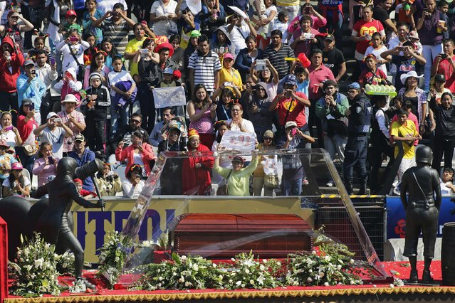 People applaud as the coffin with the remains of the late screenwriter Roberto Gomez Bolanos passes by upon arriving for a mass held in his honour at the Azteca stadium in Mexico City November 30, 2014. (Photo by Tomas Bravo/Reuters)