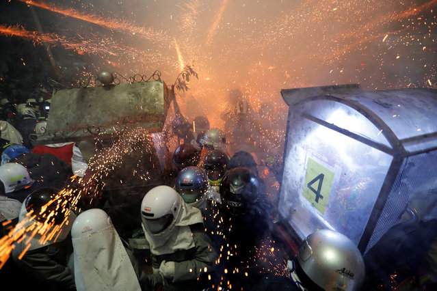 "Participants wearing motorcycle helmets get sprayed with firecrackers, during the ""Beehive Firecrackers"" festival at the Yanshui district in Tainan, Taiwan on March 1, 2018. (Photo by Tyrone Siu/Reuters)"