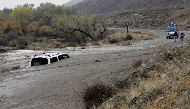 A television news crew walks away from a vehicle caught in an overnight mudslide on Soboba Road near Gilman Springs Road in San Jacinto, Calif. on Thursday, December 4, 2014. Heavy rain triggered flash floods and stranded more than three dozen people in their cars in Southern California. (Photo by Frank Bellino/AP Photo/The Press-Enterprise)