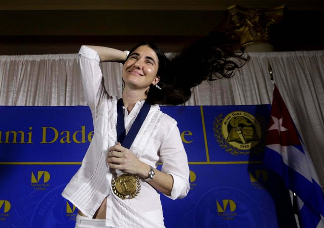 Blogger and activist Yoani Sanchez of Cuba adjusts her hair after receiving a medal from Miami Dade College president Eduardo Padron, after speaking at the Freedom Tower of Miami Dade College, on April 1, 2013. Sanchez has gained thousands of followers worldwide for her candid descriptions of modern life in Cuba on her blog Generation Y. (Photo by Lynne Sladky/Associated Press)