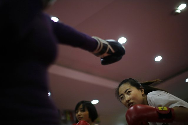 A woman dodges a punch during a boxing class at Princess Women's Boxing Club in Shanghai December 8, 2014. (Photo by Carlos Barria/Reuters)