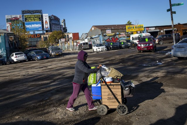 A woman selling drinks pushes a cart in the Willets Point area of Queens in New York October 30, 2015. (Photo by Andrew Kelly/Reuters)