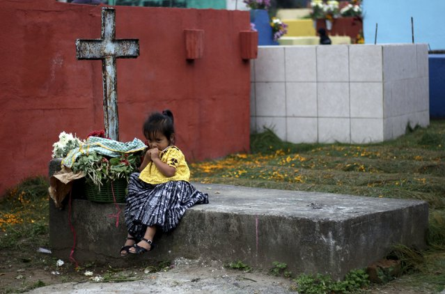 A child sits on a grave in the cemetery of Tactic, in the Alta Verapaz region, in Guatemala, November 1, 2015. People visit cemeteries and graves of deceased relatives and friends to commemorate All Saints Day, which falls on November 1. (Photo by Josue Decavele/Reuters)