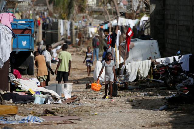 People walk down the street in front of destroyed houses after Hurricane Matthew passes Jeremie, Haiti, October 7, 2016. (Photo by Carlos Garcia Rawlins/Reuters)