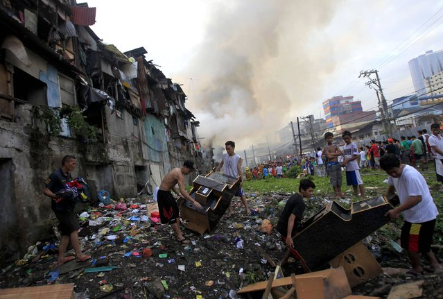 Families carry their belongings as they evacuate their homes after a fire broke out at a slum area in Manila December 11, 2014. (Photo by Romeo Ranoco/Reuters)