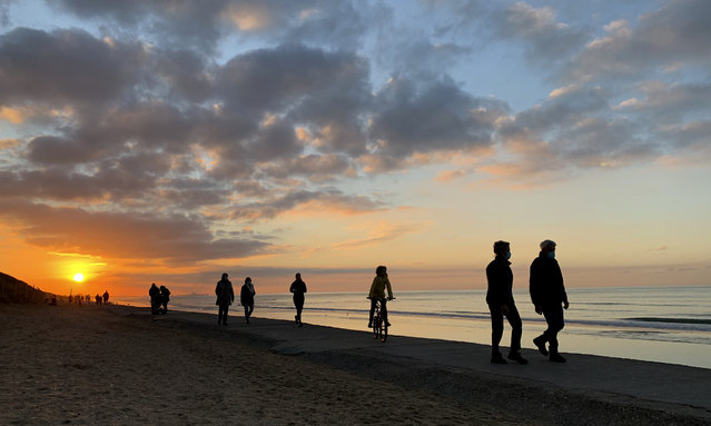 The sun begins to set as people walk along the seaside in Adinkerke, Belgium, Thursday, November 5, 2020. Seaside towns in Belgium were busier than usual due to coronavirus, COVID-19 restrictions and school holiday. (Photo by Virginia Mayo/AP Photo)