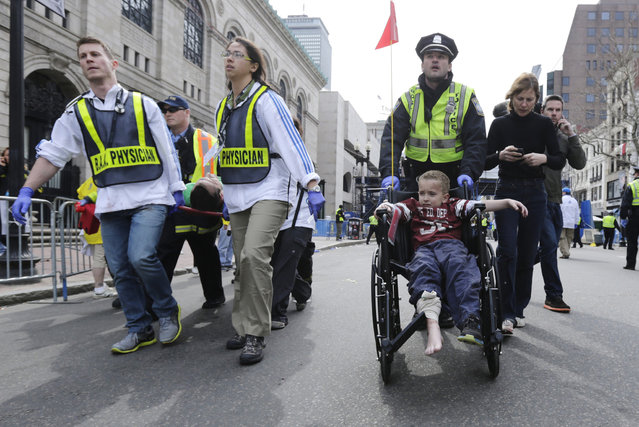 A Boston police officer wheels in injured boy down Boylston Street as medical workers carry an injured runner following an explosion during the 2013 Boston Marathon in Boston, Monday, April 15, 2013. (Photo by Charles Krupa/AP Photo)