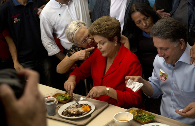In this August 27, 2014 file photo, a woman speaks strongly to Brazil's President Dilma Rousseff, who's running for reelection for the Workers Party (PT), as Rousseff makes a campaign stop at a popular restaurant in Rio de Janeiro, Brazil. (Photo by Silvia Izquierdo/AP Photo)
