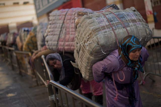 Women porters queue carry bundles for transport across the El Tarajal boarder separating Morocco and Spain's North African enclave of Ceuta, in Ceuta on December 4, 2014. (Photo by Jorge Guerrero/AFP Photo)