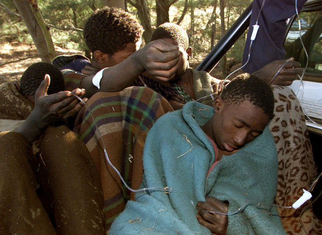 Young South African boys, survivors of a traditional initiation ceremony receive medical care before being transported to hospital June 25, 2002. (Photo by Juda Ngwenya/Reuters)