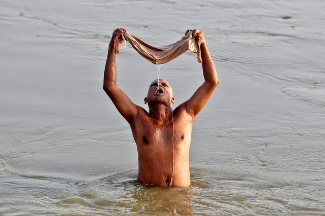 A Hindu devotee uses a cloth filter to drink water from the river Ganga, early morning in Allahabad, India, October 23, 2016. (Photo by Jitendra Prakash/Reuters)