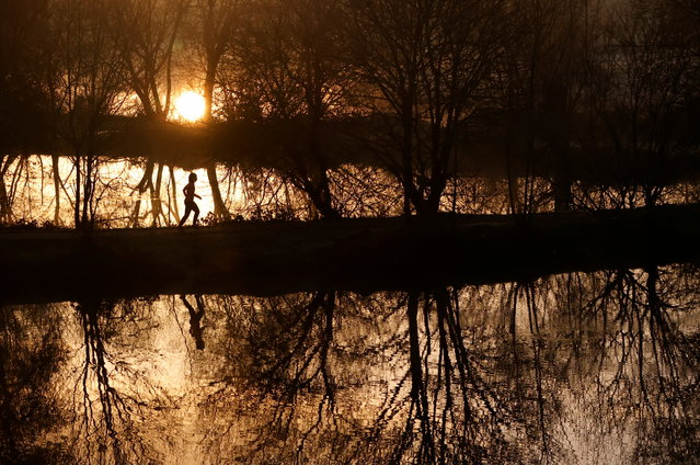A woman runs through trees in a park at sunrise in Vertou, near Nantes, France, December 9, 2020. (Photo by Stephane Mahe/Reuters)