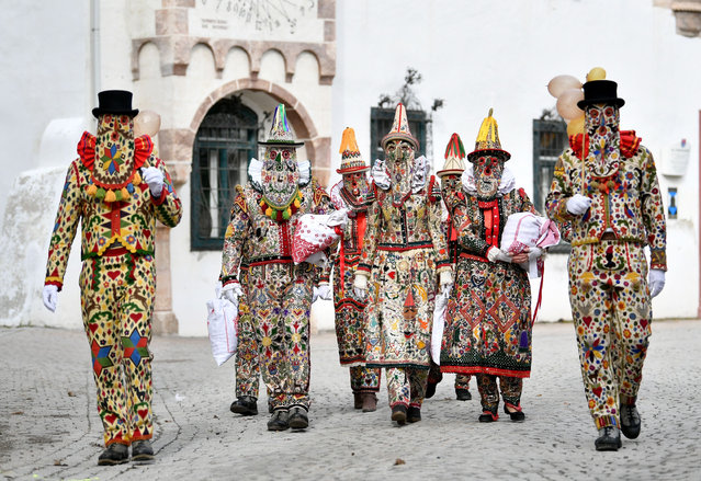 Masked participants attend a traditional carnival procession in Bad Aussee, Austria on February 25, 2020. The spring figures of the Aussee carnival wear so-called Flinserl dresses which are made of natural linen with colourful cloth patches embroidered with silver sequins. (Photo by Barbara Gindl/APA/AFP Photo)