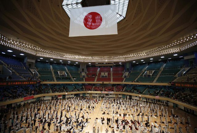 Participants show off their writings under a huge Japanese national flag at a new year calligraphy contest in Tokyo January 5, 2015. (Photo by Issei Kato/Reuters)