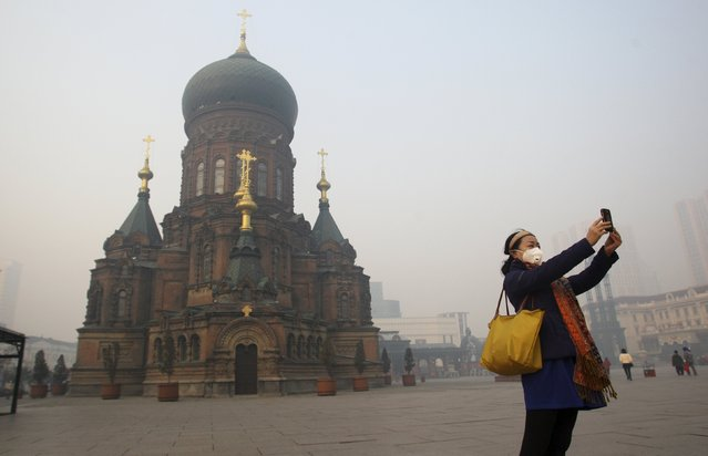 A woman wearing a mask poses for a selfie with her mobile phone on the square in front of Harbin's landmark San Sophia church, on a hazy day in Harbin, Heilongjiang province, China, November 3, 2015. (Photo by Reuters/Stringer)