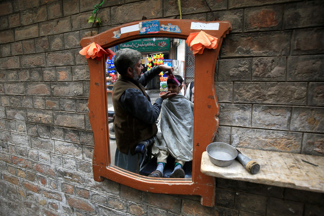 A barber gives a haircut to a customer at a roadside shop during World AIDS Day in Peshawar, Pakistan, 01 December 2020. According to doctors, cuts from razor blades that haven't undergone proper sterilization are among some of the main causes of AIDS spread. World AIDS Day, observed annually on 01 December, is dedicated to raising awareness against the spread of AIDS and HIV infections. (Photo by Arshad Arbab/EPA/EFE)