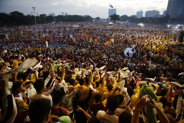 Devotees wave handkerchiefs as they sing a religious hymn before the start of the annual procession of the Black Nazarene in Manila, January 9, 2015. (Photo by Erik De Castro/Reuters)