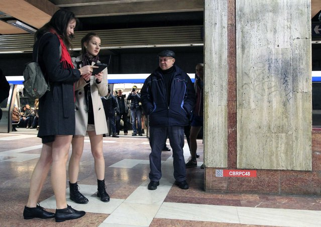 """A man looks on at two passengers without pants during """"The No Pants Subway Ride"""" in Bucharest January 11, 2015. (Photo by Radu Sigheti/Reuters)"""